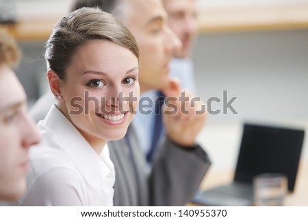 Portrait of a pretty young businesswoman sitting at a business meeting with colleagues - stock photo
