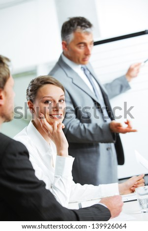 Portrait of a pretty young businesswoman smiling in a meeting with her colleagues in background - stock photo