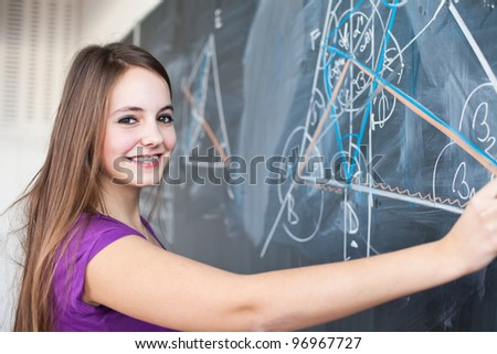 Portrait of a pretty young college student writing on the blackboard during a maths class (color toned image) - stock photo
