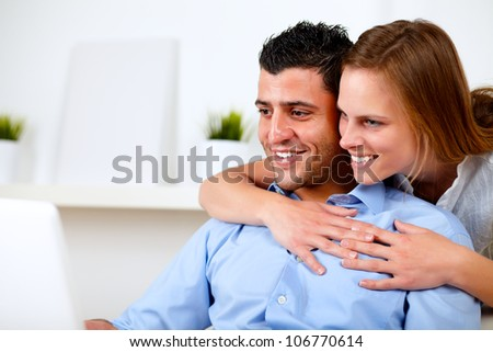 Portrait of a pretty young couple browsing Internet together on their laptop at living room at home indoor - stock photo
