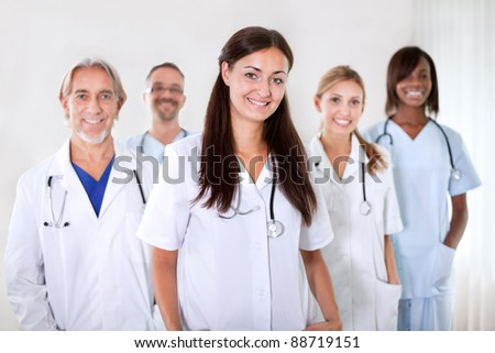 Portrait of a pretty young doctor smiling with colleagues in the background at a hospital