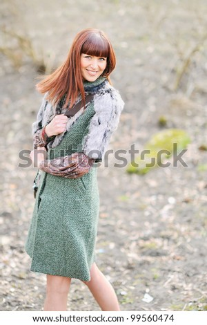 Portrait of a pretty young fashion model smiling outdoors - stock photo