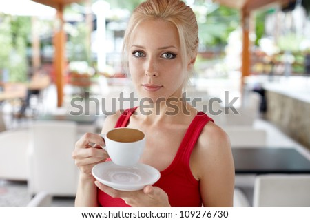 portrait of a pretty young female having a cup of coffee - stock photo