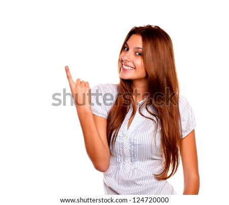 Portrait of a pretty young female with long brown hair pointing up and looking at you against white background - copyspace - stock photo