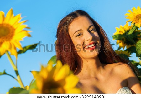 portrait of a pretty young girl in a sunflower field