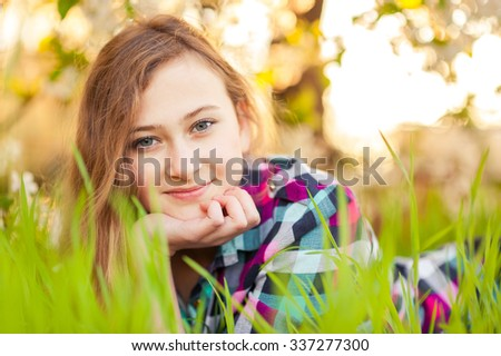 Portrait of a pretty young girl  in the checked shirt with long hair. She lies among a bright and fresh green grass. The blossoming spring trees of cherry with white flowers are on the background.  - stock photo