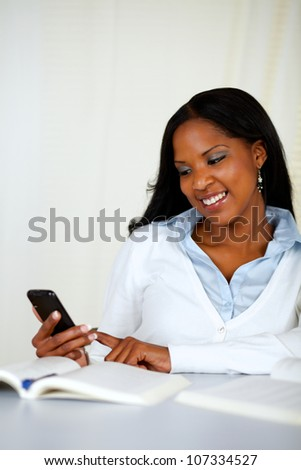 Portrait of a pretty young girl sending a sms with the mobile at soft colors composition