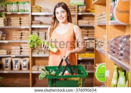 Portrait of a pretty young Hispanic brunette buying some vegetables and grains at a grocery store - stock photo