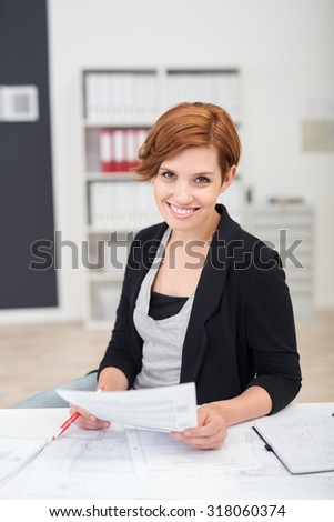Portrait of a Pretty Young Office Woman Holding Documents While Sitting at her Table and Smiling at the Camera.