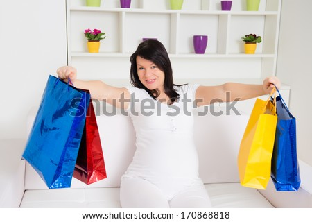 Portrait of a pretty young pregnant woman with a shopping bags - stock photo