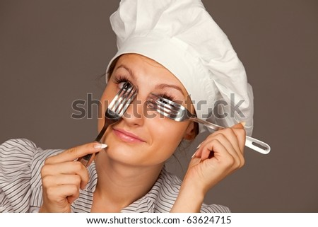 Portrait of a pretty young smiling  uniformed female Chef looking through forks - stock photo
