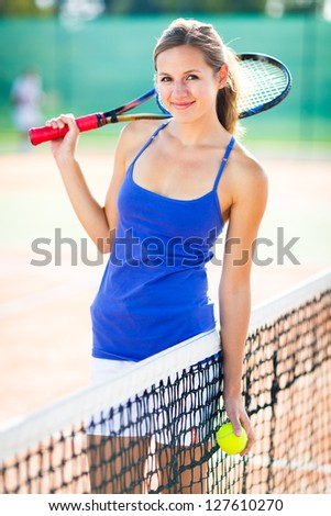 Portrait of a pretty young tennis player on the court - stock photo
