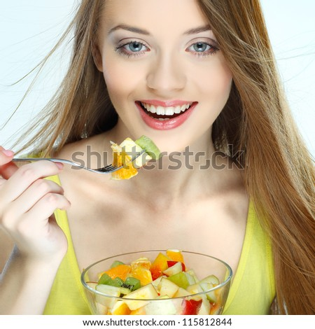 Portrait of a pretty young woman eating fruit salad isolated on  a white background - stock photo