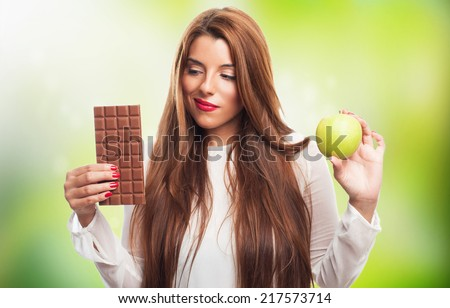portrait of a pretty young woman having a dilemma with her diet - stock photo