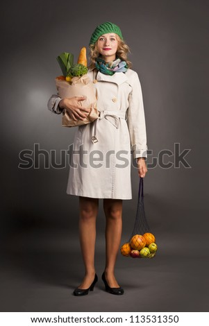 Portrait of a pretty young woman holding a grocery bag and smiling against black background - stock photo