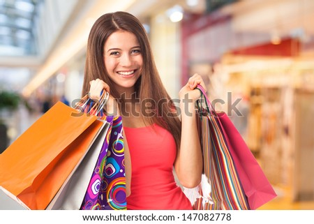 Portrait of a pretty young woman holding shopping bags in a supermarket - stock photo