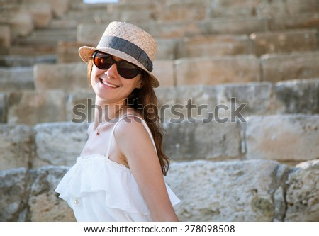 Portrait of a pretty young woman in a hat on stone background - stock photo