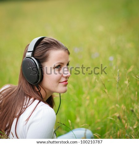 portrait of a pretty young woman listening to music on her mp3 player outdoors (daydreaming)