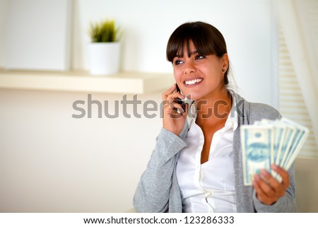 Portrait of a pretty young woman looking at her right and speaking on cellphone with money