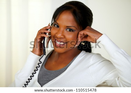 Portrait of a pretty young woman looking at you while talking on phone at soft colors composition