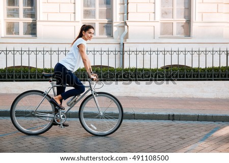 Portrait of a pretty young woman on bicycle in the city street