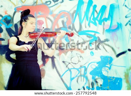 Portrait of a pretty young woman playing the violin, applied filter instagram style - stock photo