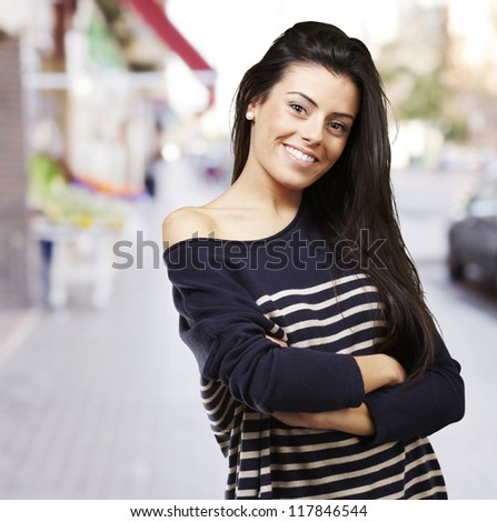 portrait of a pretty young woman smiling against a street background - stock photo
