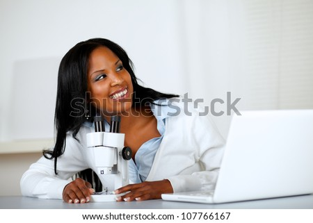 Portrait of a pretty young woman using a microscope and looking to his left at laboratory