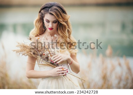 Portrait of a pretty young woman walking outdoors near a lake with reed in their hands. - stock photo