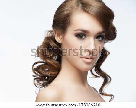 Portrait of a pretty young woman with a beautiful hairstyle and makeup. Girl with wavy hair - stock photo