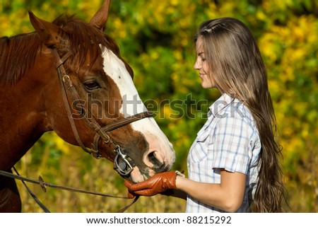 portrait of a pretty young woman with a browne horse - stock photo