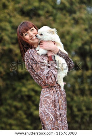 Portrait of a pretty young woman with her dog - stock photo