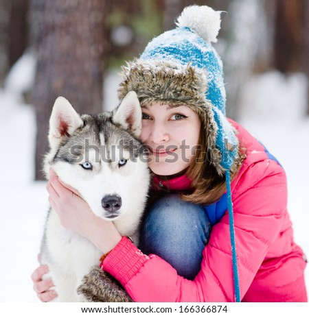Portrait of a pretty young woman with her pet dog - stock photo