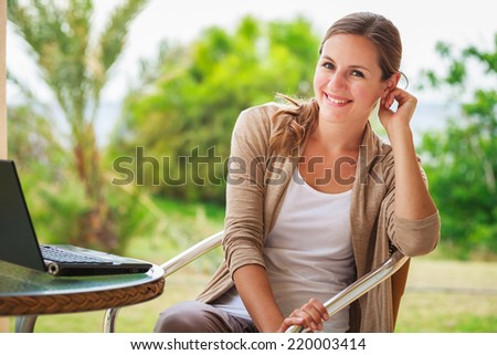 Portrait of a pretty young woman working on her computer on a terrace of her house - stock photo