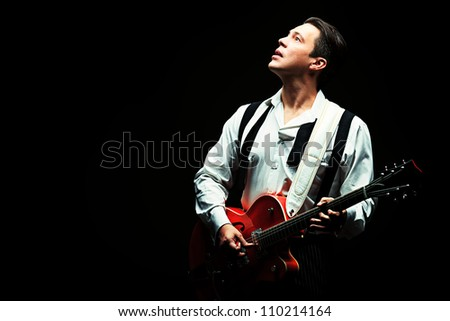 Portrait of a professional artist playing on guitar. Over black background. - stock photo