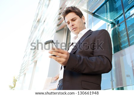 "Portrait of a professional business man holding a ""smart phone"" and dialing while leaning on the glass banister of a modern office building in the city. - stock photo"