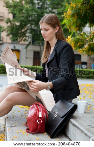 Portrait of a professional business woman sitting on the steps of an office building reading the stock market pages of a financial newspaper, thoughtful outdoors. Corporate business financial city. - stock photo