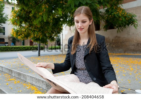 Portrait of a professional business woman sitting on the stone steps of an office building reading the stock market pages of a financial newspaper, smiling outdoors. Corporate business financial city. - stock photo