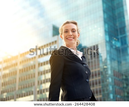 Portrait of a professional business woman smiling outside in the city with buildings in the background  - stock photo