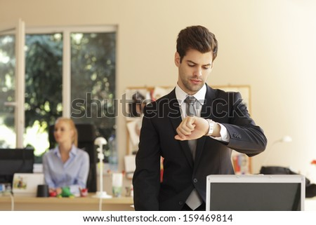 Portrait of a professional businessman sitting on office desk and looking at his watch