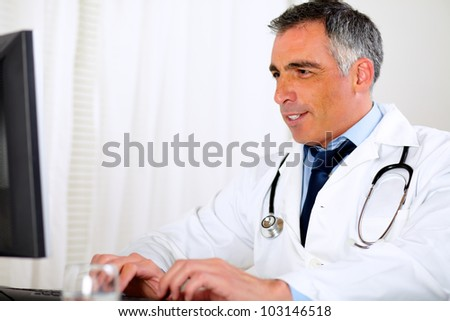 Portrait of a professional doctor using a computer at the hospital office - stock photo