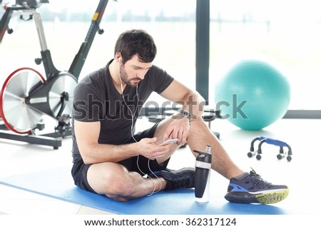 Portrait of a professional fitness instructor listening music at his mobile phone while taking break after workout at gym.