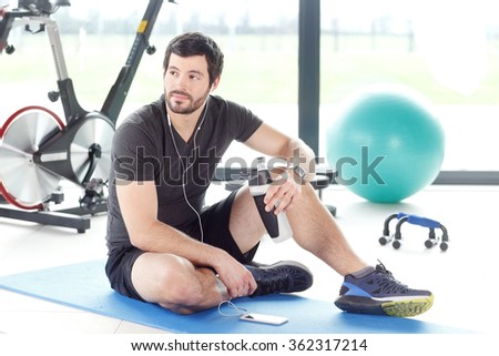 Portrait of a professional fitness instructor listening music at his mobile phone while taking break after workout at gym. - stock photo
