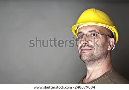 Portrait of a proficient worker with yellow hard hat - stock photo