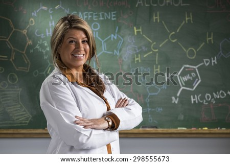 Portrait of a proud Hispanic teacher in front of a chalkboard in a classroom setting