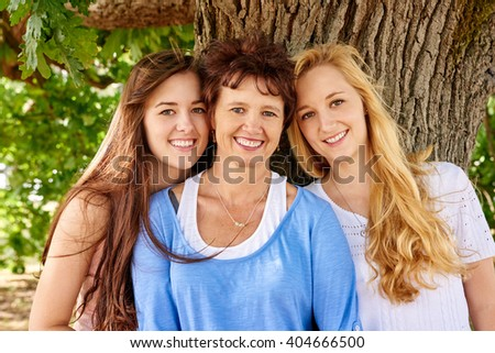 Portrait of a proud mature woman with her two beautiful adult daughters standing lovingly close their mother and smiling at the camera under a large tree - stock photo