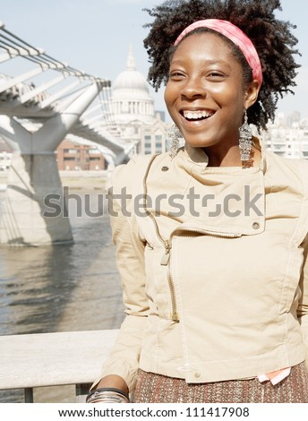 Portrait of a quirky black woman on vacations, visiting London city with the Millennium Bridge and St Paul's Cathedral behind her.