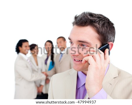 Portrait of a radiant businessman on phone in front of his team - stock photo