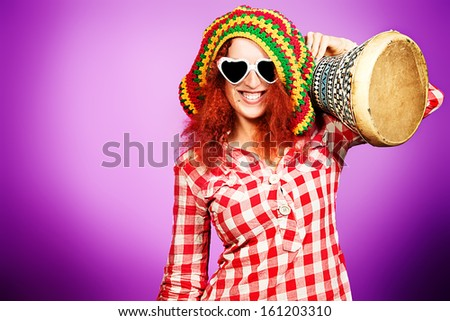 Portrait of a rastafarian girl playing her drum. - stock photo