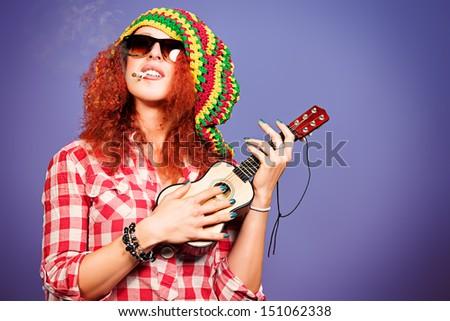 Portrait of a rastafarian girl playing her guitar. - stock photo